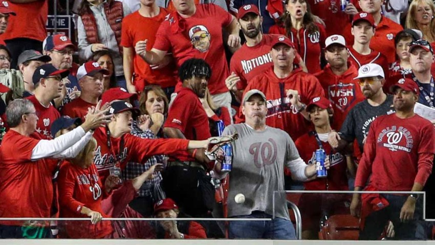While holding two Bud Light beer cans, baseball fan, Jeff Adams, is hit in the chest with the home run ball hit by Yordan Alvarez #44 of the Houston Astros (not pictured) in the second inning during Game 5 of the 2019 World Series between the Houston Astros and the Washington Nationals at Nationals Park on October 27, 2019 in Washington, DC.