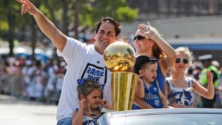 Dallas Mavericks owner Mark Cuban rides with the NBA Championship basketball trophy and his family wife Tiffany, holding son Jake, and daughters Alexis Sofia, right, and Alyssa, during the team's victory parade in downtown Dallas, Thursday, June 16, 2011.