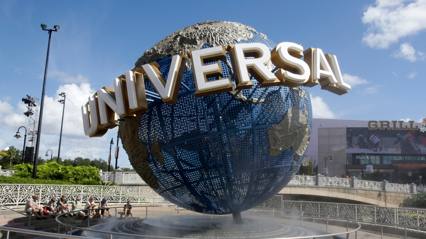 In this Oct. 22, 2015 file photo, park guests relax and cool off with a water mist under the globe at Universal Studios City Walk in Orlando, Fla.