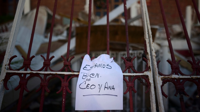 "A note that reads ""We're well. Ceo and Ana,"" hangs on a fence"