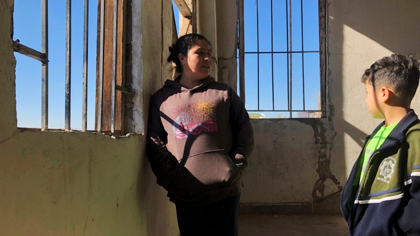 Enma Floriana chats with her 13-year-old son in the stairway of a migrant shelter in Mexicali, Mexico.