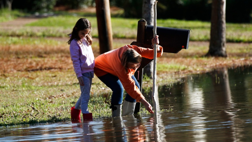 Barbara Beavers and her daughter measure rising floodwaters in Mississippi