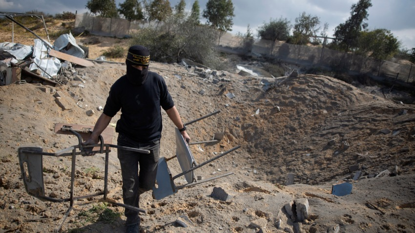A masked Palestinian militant checks the damage following overnight Israeli airstrikes on an Islamic Jihad military base in the town of Khan Younis, Southern Gaza Strip, Monday, Feb. 24, 2020.