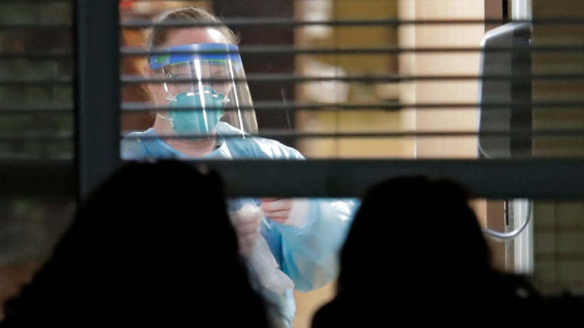 In this March 10, 2020, file photo, a worker wearing protective gear is seen through a window as she works in a room of a woman who has tested positive for the new coronavirus, as her daughters look in from outside the window, at the Life Care Center in Kirkland, Wash., near Seattle.