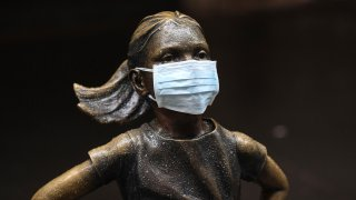 """In this file photo, a surgical mask is placed on The """"Fearless Girl"""" statue outside the New York Stock Exchange on Thursday, March 19, 2020, in New York."""