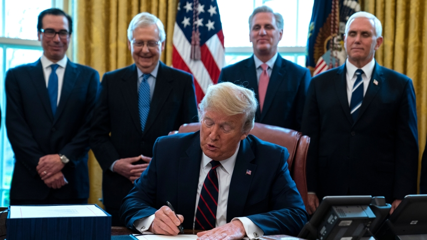 In this March 27, 2020 file photo, President Donald Trump signs the coronavirus stimulus relief package in the Oval Office at the White House in Washington, as Treasury Secretary Steven Mnuchin, Senate Majority Leader Mitch McConnell, R-Ky., House Minority Leader Kevin McCarty, R-Calif., and Vice President Mike Pence watch. Payments from a federal coronavirus relief package could take several weeks to arrive. While you wait, prep your finances and make a plan for using any money you receive.