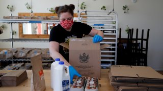 Monica Mileur packs grocery items into a box