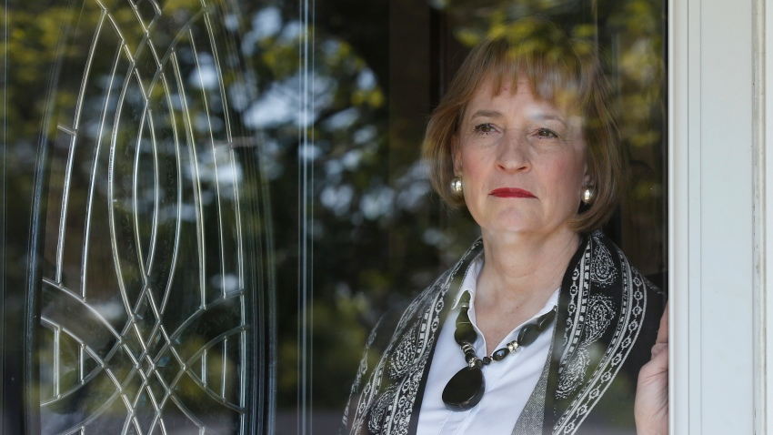 Lynne Gist looks out of the front door of her home