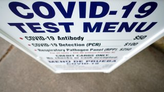 A sign outside Principle Health Systems and SynerGene Laboratory lists COVID-19 tests available Tuesday, April 28, 2020, in Houston.