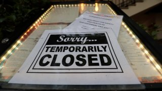 FILE - In this April 28, 2020 file photo, a closed sign is posted at a restaurant along the River Walk in San Antonio.