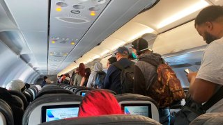 FILE - In this Monday, April 27, 2020, file photo, provided by Vince Warburton, passengers get off an American Airlines flight after they landed at Los Angeles International Airport in Los Angeles.