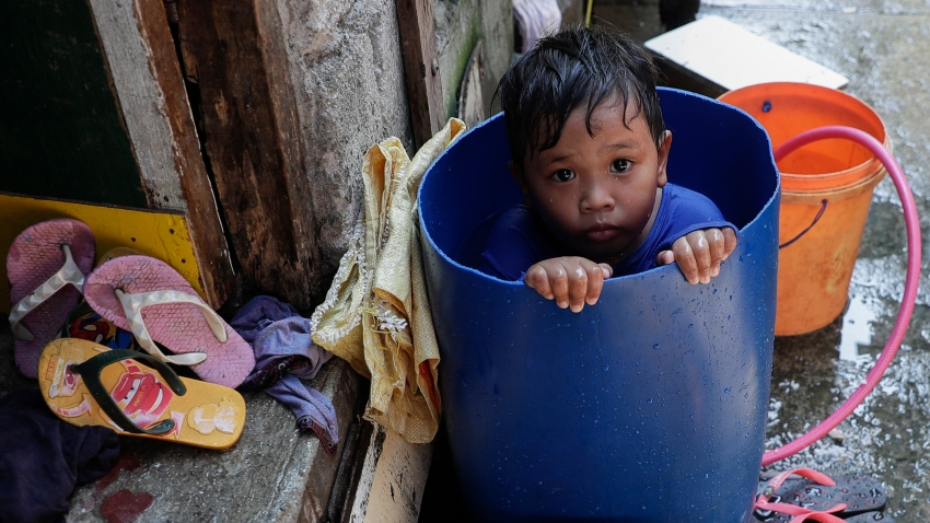 A boy takes a bath inside a plastic container at a coastal village in Cavite province, south of Manila, Philippines, during a continuing enhanced community quarantine to prevent the spread of the new coronavirus, Thursday, May 7, 2020.