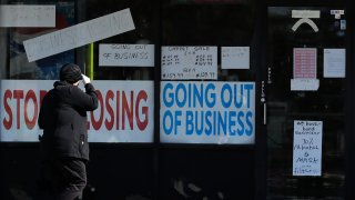 A woman looks at signs at a store in Niles, Ill., Wednesday, May 13, 2020.
