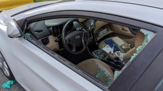 a parked car with a broken driver's side window after a smash-and-grab break-in