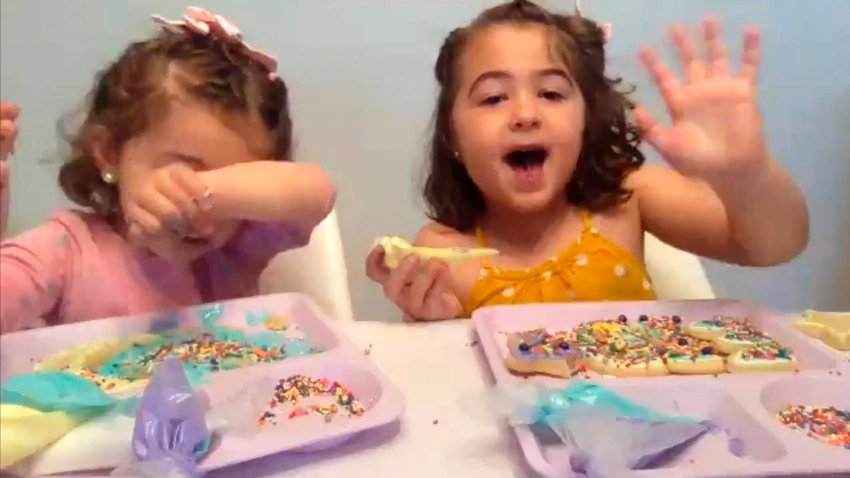 In this May 23, 2020, image from video, Liyana Mujovic, 2, her sister Suhaila, 5, and a group of friends decorate cookies for Eid al-Fitr over Zoom as they celebrate the end of a month-long fast, marking the end of Ramadan.