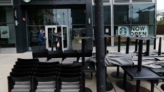 FILE - In this May 21, 2020 file photo, patrons to a Starbucks in the Chicago neighborhood of Hyde Park walk past stacked chairs and tables.