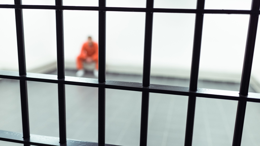 prisoner sitting on bench with prison bars on foreground