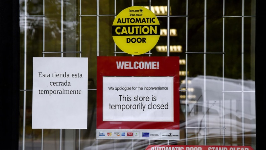 "A ""Temporarily Closed"" sign is seen in front of a store amid the coronavirus pandemic on May 14, 2020, in Arlington, Virginia."