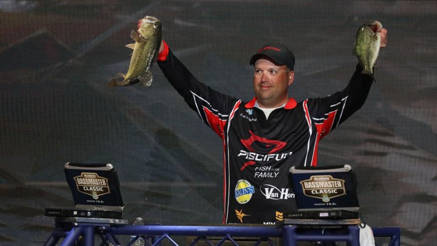 Previous Bassmaster holding up a bass.