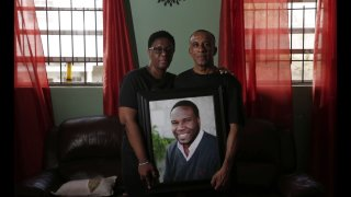 In this Sept. 25, 2018 file photo, Allison and Bertrum Jean pose as they hold a portrait of their late son, Botham Shem Jean.