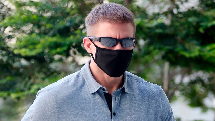 In this May 13, 2020, photo, Brian Dugan Yeargan, wearing a face mask and sunglasses, walks outside the Singapore State Court in Singapore. The 44-year-old American pilot has been jailed for four weeks for breaching a quarantine order in Singapore.
