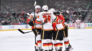 Elias Lindholm #28, Sean Monahan #23 and the Calgary Flames celebrate a goal against the Dallas Stars at the American Airlines Center on Dec. 22, 2019 in Dallas, Texas.
