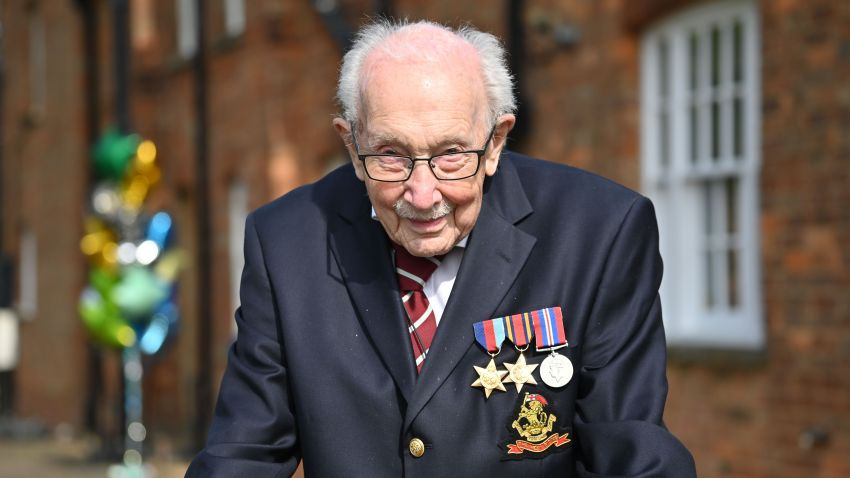 In this April 16, 2020, file photo, British World War II veteran Captain Tom Moore, 99, poses doing a lap of his garden in the village of Marston Moretaine, 50 miles north of London.