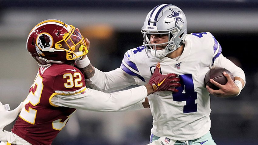 Dak Prescott #4 of the Dallas Cowboys fends off a tackle attempt by Jimmy Moreland #32 of the Washington Redskins in the third quarter in the game at AT&T Stadium on December 29, 2019 in Arlington, Texas.