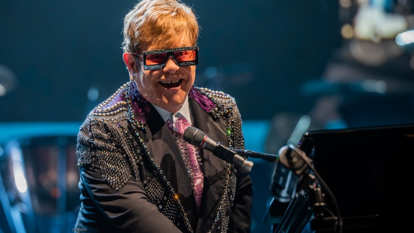 "Elton John is hosting a ""living room"" concert aimed at bolstering American spirits during the coronavirus crisis and saluting those countering it."