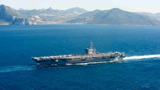 In this June 13, 2016, file photo provided by the U.S. Navy, the aircraft carrier USS Dwight D. Eisenhower (CVN 69) transits the Strait of Gibraltar into the Mediterranean Sea.