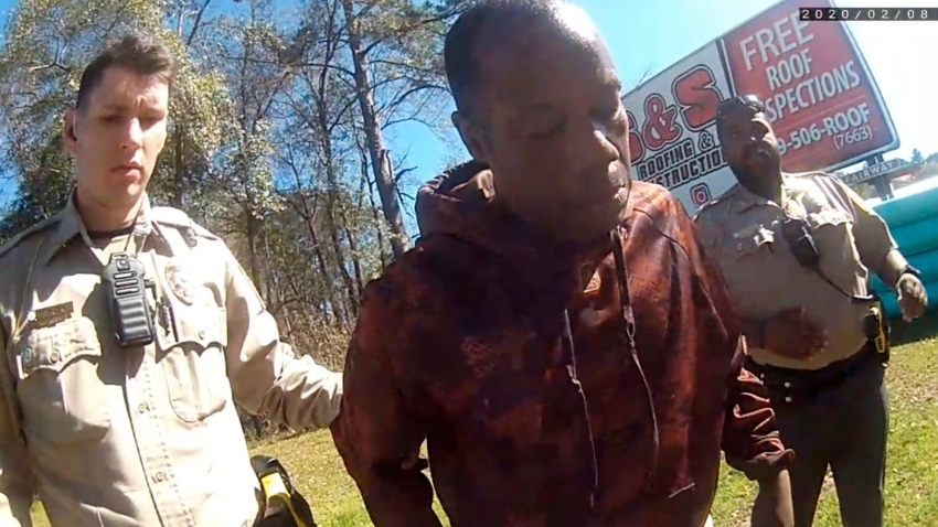 In this still image from body camera video released by the Valdosta police, Antonio Arnelo Smith, center, recovers after being slammed face-first to the ground by a Valdosta police sergeant, in Valdosta, Ga., on Feb. 8, 2020. The video shows Smith handing his driver's license to a police officer and answering questions cooperatively before a second officer, Sgt. Billy Wheeler, approaches him from behind, wraps him in a bear hug and slams him face-first to the ground. Smith is crying in pain when he's told there's a warrant for his arrest. Officers are then told the warrant was for someone else.