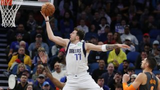The Dallas Mavericks' Luka Doncic (77) scores easily in front of the Orlando Magic's Nikola Vucevic, right, at the Amway Center in Orlando, Fla., on Friday, Feb. 21, 2020.