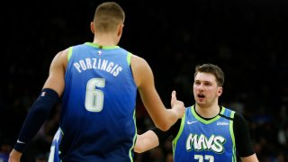 Luka Doncic #77 of the Dallas Mavericks congratulates teammate Kristaps Porzingis #6 on scoring against the San Antonio Spurs during second-half action at AT&T Center on February 26, 2020 in San Antonio, Texas. The Mavs defeated the Spurs 109-103.