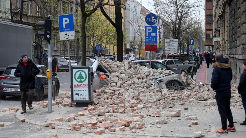 Fallen rubble smashes a parked car
