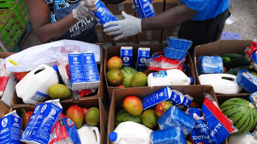 Workers fill boxes of food from the Second Harvest Food Bank of Central Florida to be distributed to needy families at a mobile food drop event at the Impact Outreach Ministry on April 6, 2020 in Orlando, Florida.