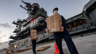 Sailors assigned to the aircraft carrier USS Theodore Roosevelt (CVN 71) carry food supply boxes
