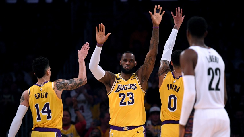 LeBron James #23 of the Los Angeles Lakers celebrates his basket and a Brooklyn Nets foul with Danny Green #14 and Kyle Kuzma #0 during the first half at Staples Center on March 10, 2020 in Los Angeles, California.
