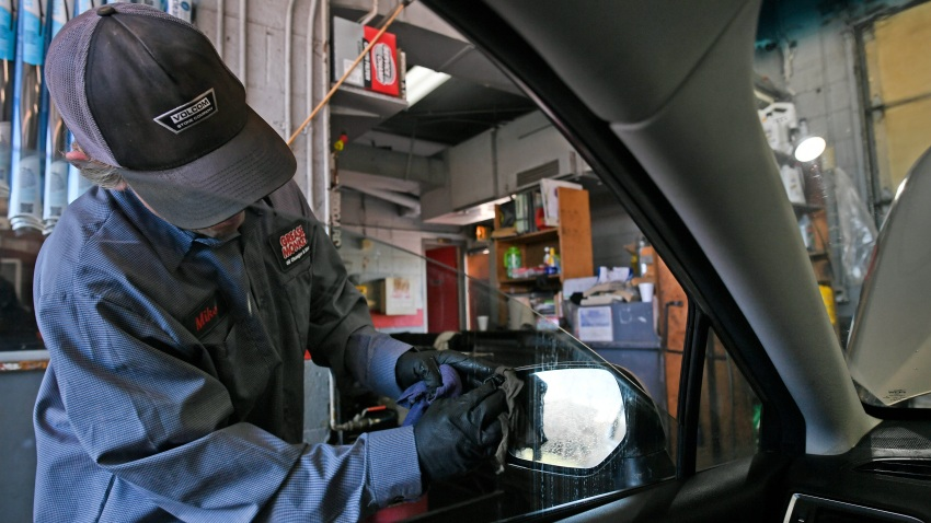 Mike Buckley washes a side mirror as he and his crew complete an oil change while passengers stay in their cars at Grease Monkey on March 23, 2020, in Boulder, Colorado.