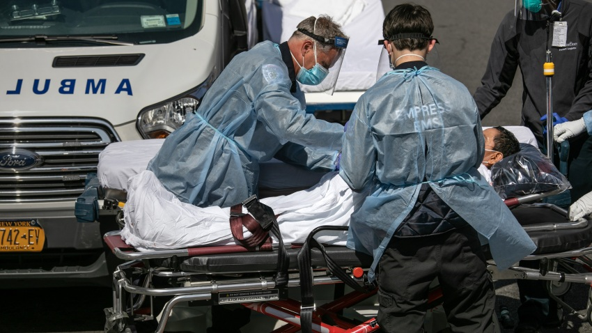 Medics and hospital workers tend to a COVID-19 patient outside the Montefiore Medical Center Moses Campus on April 7, 2020 in New York City.