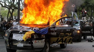 Demonstrators burn police vehicles during a protest following the death of a young man while in police custody in Guadalajara, Mexico