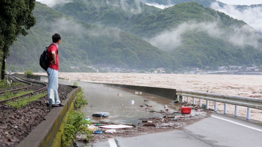 A man looks at the overflowing kuma river caused by heavy rain in Yatsushiro, Kumamoto prefecture on July 4, 2020.