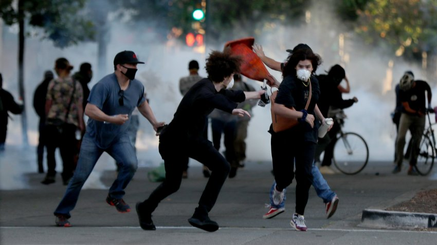 Protesters run away as police shoot tear gas and flash grenades to disperse the crowd on Broadway near the Oakland Police Department during the fourth day of protests over George Floyd's death by the Minneapolis police in Oakland, Calif., on June 1, 2020.