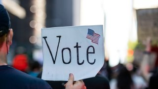"""In this June 14, 2020, file photo, a protester holds a sign that says """"Vote"""" with an American Flag as they march through the streets of New York City."""