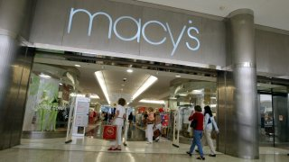 Customers walk out of a Macy's store