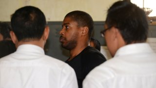 Vontrey Clark (C), a former US policeman, is escorted by Indonesian police from a holding cell in Denpasar to Ngurah Rai international airport as he is deported from the resort island of Bali on September 2, 2015.