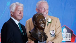 Dallas Cowboys owner Jerry Jones and presenter Jimmie Johnson pose with Jones' bust during the Pro Football Hall of Fame Enshrinement Ceremony at Tom Benson Hall of Fame Stadium on August 5, 2017 in Canton, Ohio.
