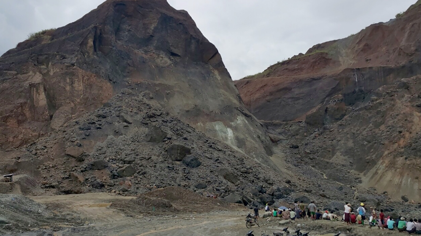In this photograph taken on May 24, 2016, rescue workers gather beside a landslide in a jade mining area on the outskirts of Hpakant in Myanmar's northern Kachin State.