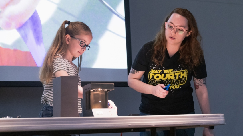 woman and girl performing presentation at perot museum