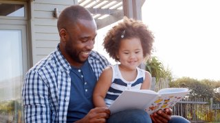Man reads book to daughter
