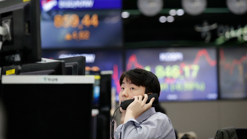 In this April 16, 2020, file photo, a currency trader watches computer monitors at the foreign exchange dealing room in Seoul, South Korea.